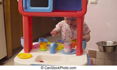 Little baby girl playing with water on toy kitchen table