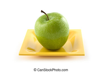 Granny Smith apple on yellow ceramic plate isolated on white...
