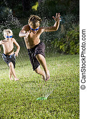 Boys running fast through lawn sprinkler - Focus on boy, 9...