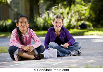 Girls playing with sidewalk chalk - Two girls, 7 years,...