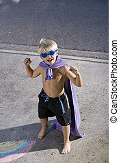 Superhero flexes his muscles - Cute boy, 7 years, in pretend...