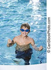 Boy with goggles in swimming pool - Boy, 9 years, having fun...