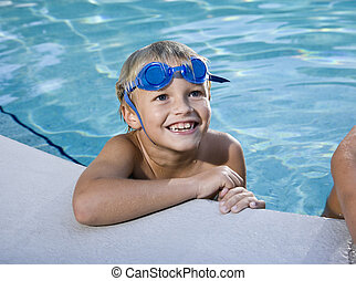 Boy grinning, hanging on to side of swimming pool