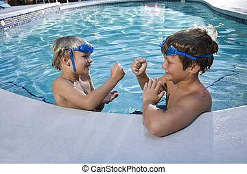 Boys playing games at edge of swimming pool