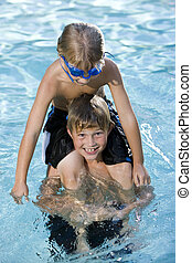 Boy sitting on brother's shoulders in pool - Boys, 7 and 9...