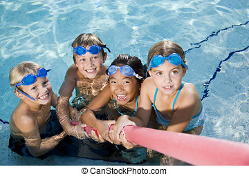 Children playing tug of war in pool - Multiracial friends...