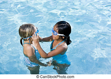 Girl in swimming pool help friend with goggles - Girls, 7...