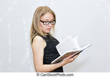 young woman in black dress with glasses reading a book