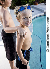Boy with brother grinning at side of swimming pool - Boys, 7...