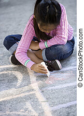 Asian girl drawing on ground with sidewalk chalk - Asian...