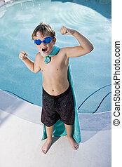 Boy superhero protecting the pool - Boy, 9 years, playing by...