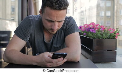 Young man with smartphone in cafe
