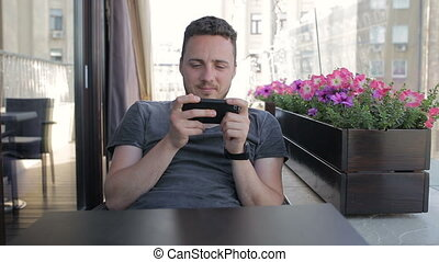 Man is playing on the phone in a cafe