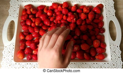 Bright red ripe strawberries and human hand
