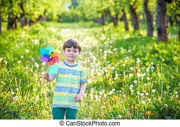 Portrait of a happy cute little boy holding pinwheel at the park