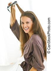 smiling young woman straightening hair with straightener