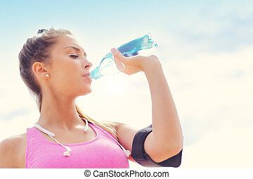 Woman with bottle of water after jogging on the beach -...