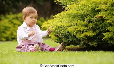 Cute little baby-girl learning to crawl on the green meadow in the city park.