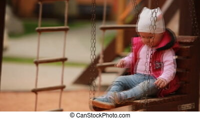 Adorable baby girl enjoying a swing ride on a playground in...