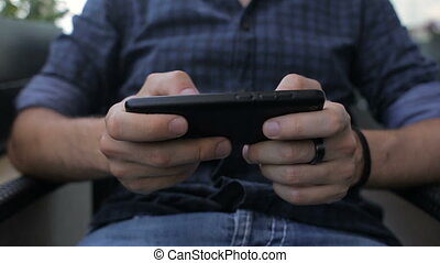 Young man playing game on smartphone sitting in cafe.