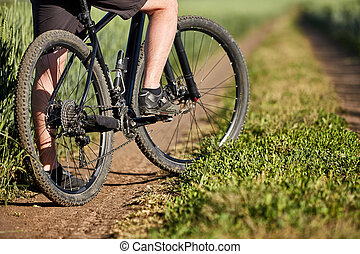 Closeup of cyclist man legs with mountain bike on outdoor...