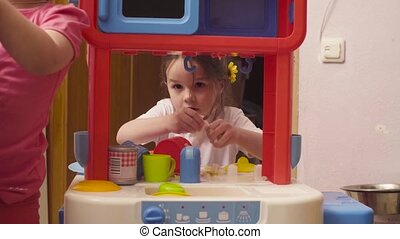 Little girl playing with dishes and food on toy kitchen...