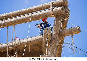 Extreme professional videographer during shooting on climbing tower working under extreme conditions