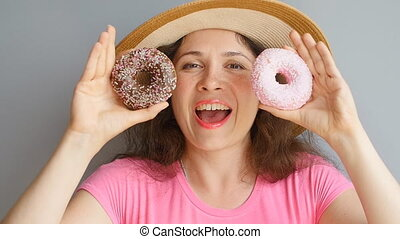 Young woman is holding donuts against her eyes and smiling -...