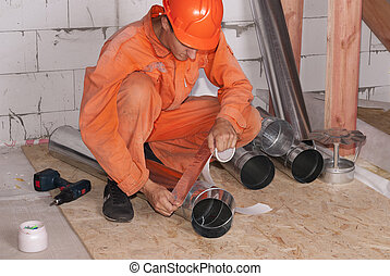 air duct installation - worker in the attic connects metal...