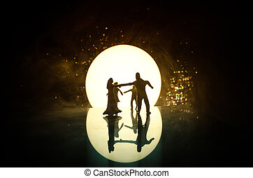 Silhouettes of toy couple dancing under the Moon at night. Figures of man and woman in love dancing at moonlight