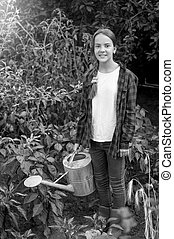 Black and white image of happy young girl in red rubber boots watering vegetables at garden
