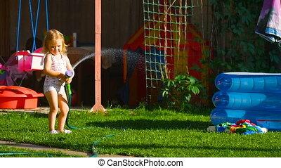 Little girl watering lawn - Little girl watering in garden...