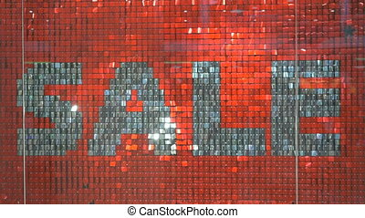 Word SALE in silver color on red background. Close-up