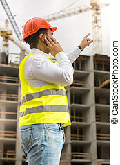 Young businessman in hardhat and safety vest talking by phone at construction site