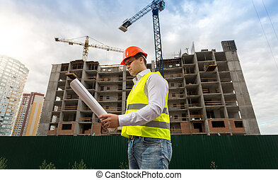 Young construction engineer in hardhat on building site with...