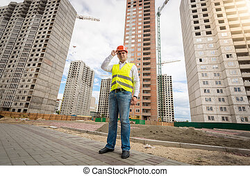 Businessman in hardhat and safety vest standing on building site