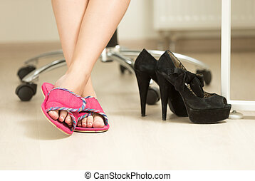 Closeup photo of businesswomen feet in slippers under table