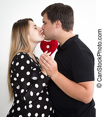 Portrait of young kissing pregnant couple in stylish clothes