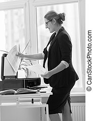 Young businesswoman in black suit making copies of documents...