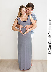 Happy hugging pregnant couple holding hands in shape of...