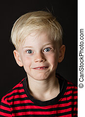 Cute wide eyed little blond boy with a missing front tooth...