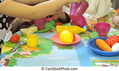 Children playing with plastic tableware. Close up