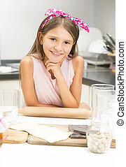Portrait of cute girl with pink bow on hair posing with...