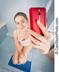 Woman sitting on toilet and making selfie on smartphone