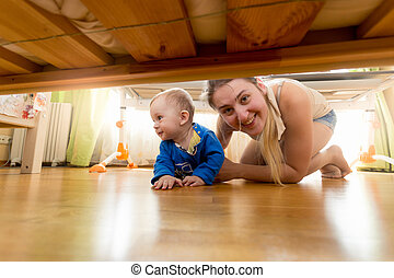Happy mother and baby boy looking under the bed