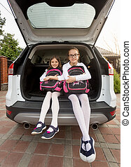 Two smiling schoolgirls sitting in open car trunk with...