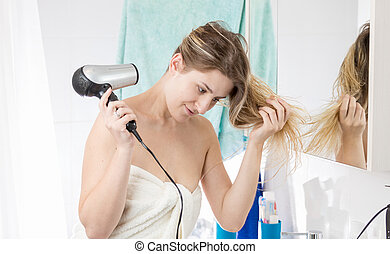 Woman drying hair with hairdryer after having bath