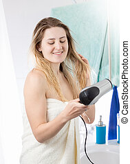Woman drying hair in bathroom after having shower