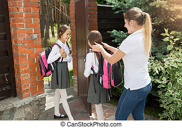 Caring mother seeing off her daughters to school