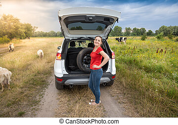 Young woman posing with spare wheel at broken car in the...